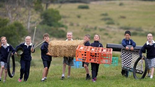 Kids at Emmaus Catholic Primary School in Mt.Clear playing on unconventional play items, hay bales, poles, tyres etc. Year 3/4 get ready for action.